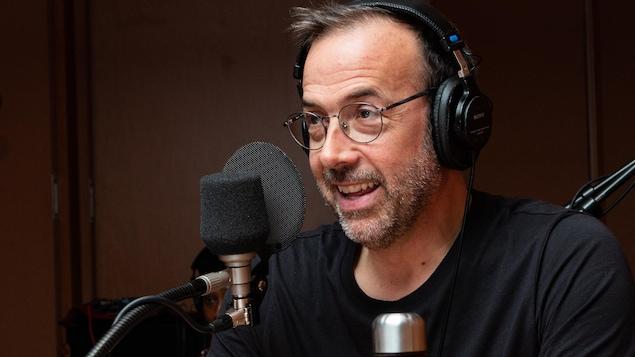 Un comédien portant des lunettes sourit en regardant quelqu'un devant un micro.