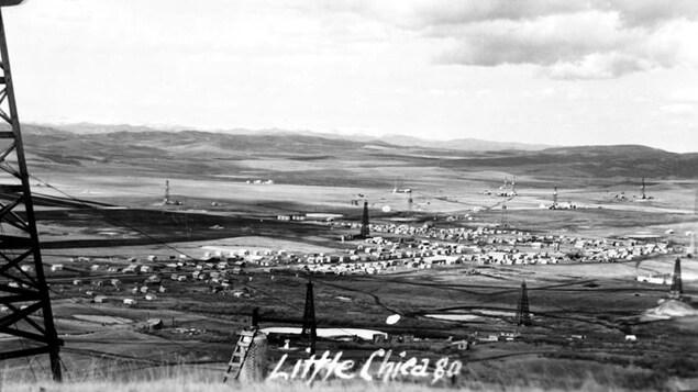 Une ancienne photo d'une petite ville vue de loin.
