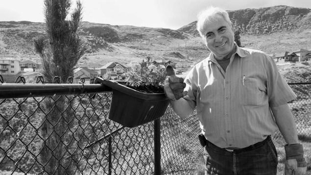 Robert Fillion dans un cour avec des gants de jardinage.