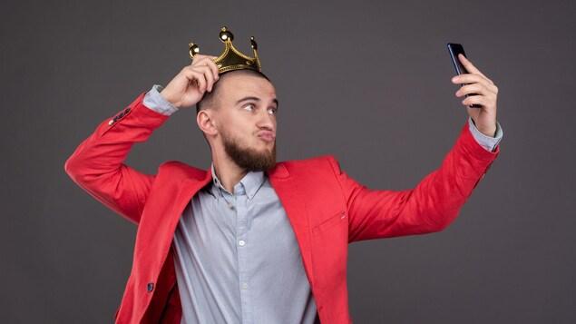 Un homme portant une couronne prend un égoportrait.