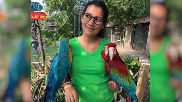 La femme tient deux perroquets sur ses bras.