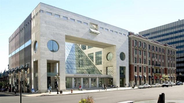 Une vue en angle de la façade du bâtiment et de la rue. La photo est prise en été.