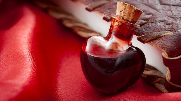 Une fiole en forme de cœur qui contient un liquide rouge.
