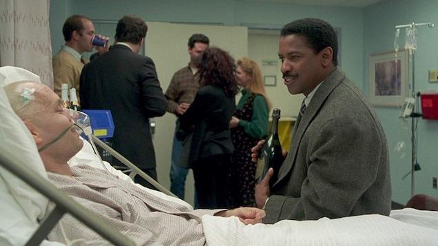 Un homme est dans un lit d'hôpital alors qu'un autre est assis à ses côtés.