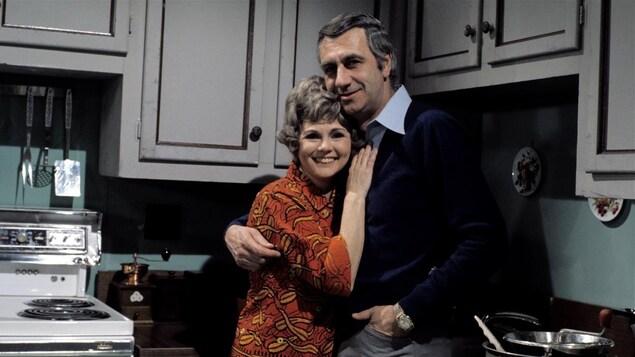 Photo prise sur le plateau de Quelle famille!, Janette Bertrand et Jean Lajeunesse sont enlacés dans la cuisine du plateau de télévision.