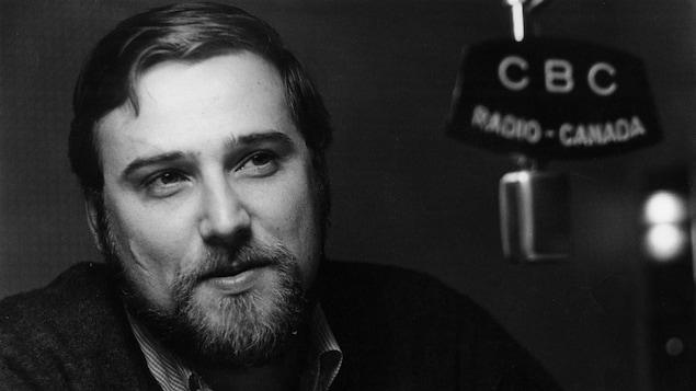 Une photo en noir et blanc d'un homme qui porte une barbe et qui sourit à un micro de Radio-Canada.