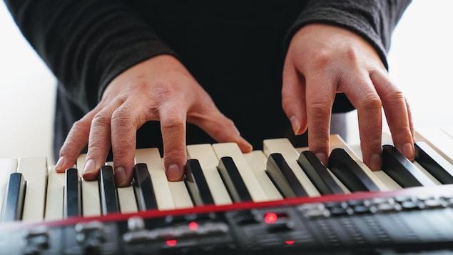 Des mains jouent des notes de musique sur un piano.