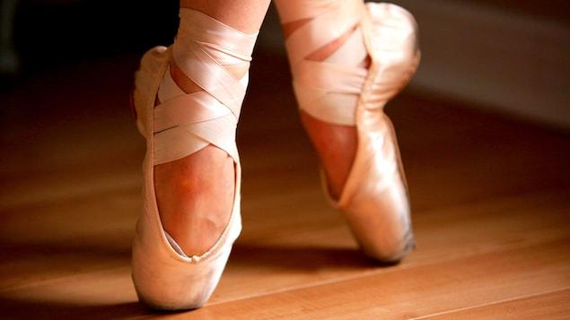 Des pieds de ballerine en pointe sur un plancher de bois