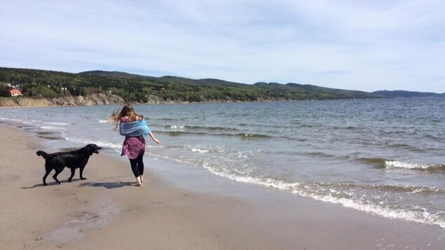 Une femme marche avec son chien sur la plage sablonneuse de Cap-aux-Os