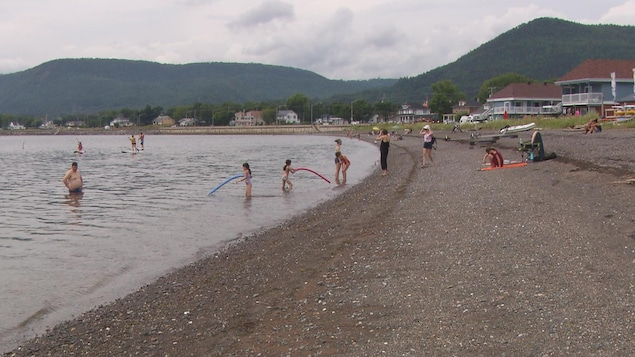 Des baigneurs profitent de l'eau par une journée nuageuse.