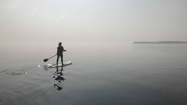 Une personne à planche à pagaie navigue dans la brume au large du Havre-Saint-Pierre.