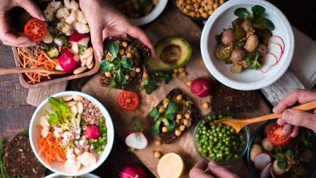 Différents plats végétaliens avec des petits pois, des champignons et différentes salades sont sur une table.