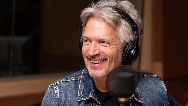 Claude Meunier, portant des écouteurs dans un studio radio, sourit.
