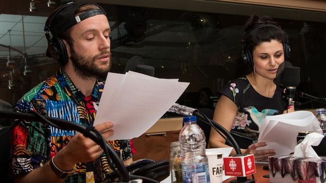 Les deux comédiens lisent leur texte sur des feuilles.