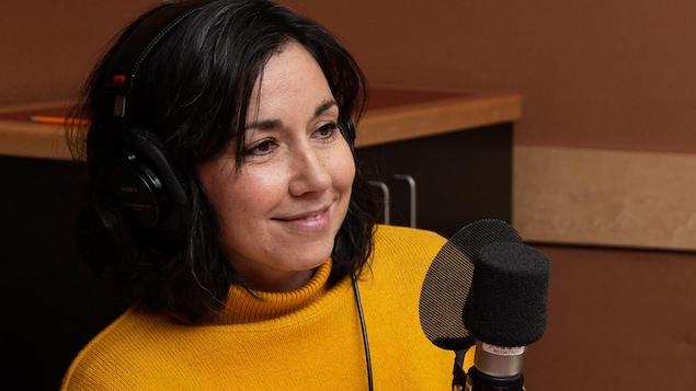 L'autrice vêtue d'un pull jaune sourit à l'animatrice.