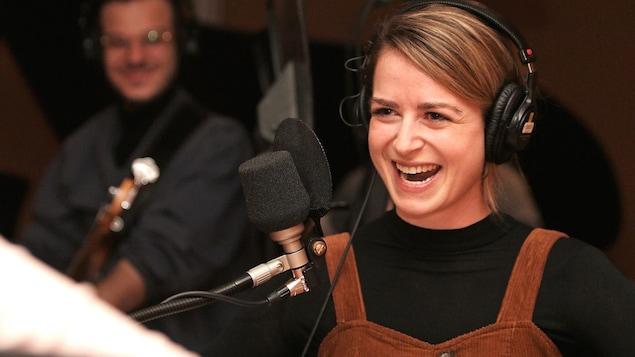 Une femme rit devant un micro dans un studio.