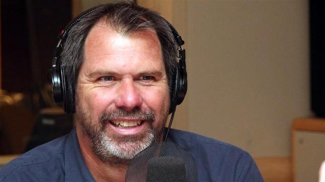 Un homme avec un casque d'écoute sur la tête sourit devant un micro.