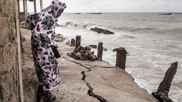 Une femme marche en regardant par terre près d'un bord de mer.