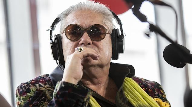 Un homme portant des écouteurs et des lunettes fumées porte sa main devant sa bouche.