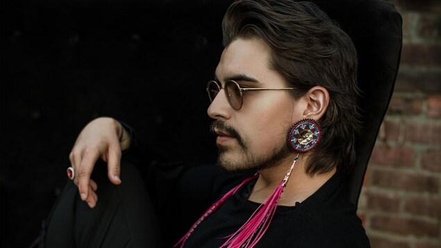 Un homme qui porte des lunettes fumée et des boucles d'oreilles ornementales est assis.