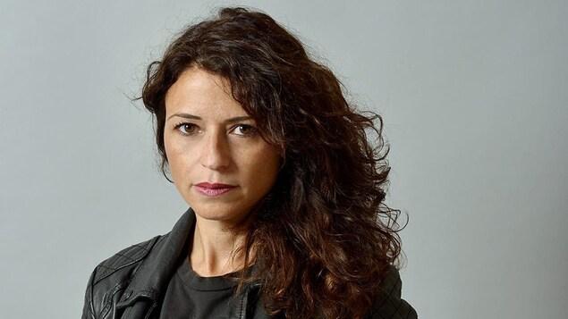 Portrait de Karine Tuil, qui porte de longs cheveux bouclés