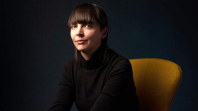 Une femme est assise sur un fauteuil et regarde la caméra.