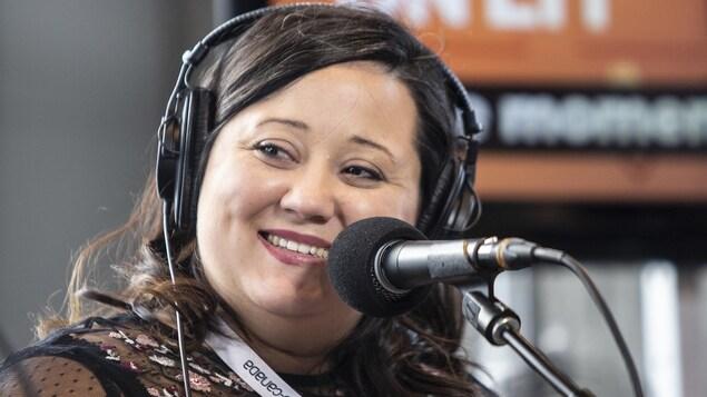 Une femme portant des écouteurs sourit devant un micro.