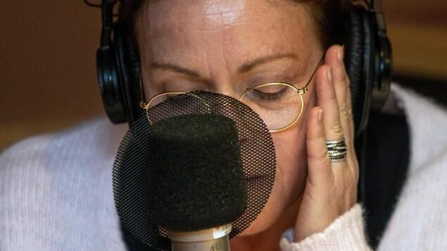 Une femme tient sa main sur gauche devant un micro.
