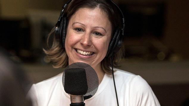 L'autrice Michèle Nicole Provencher sourit devant un micro.