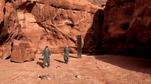 Un monolithe en métal est planté dans le désert, tandis que deux hommes marchent autour.