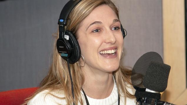 L'actrice Mylène Mackay rit devant un micro.