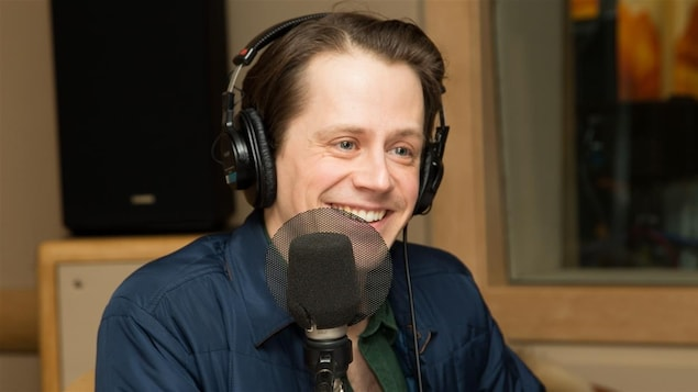 Un homme devant un micro affiche un sourire éclatant.
