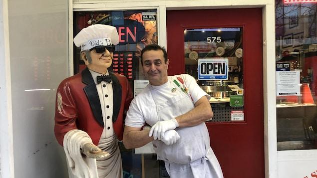 M. Did pose aux côtés d'une statue de serveur habillé en blanc avec un veston rouge.