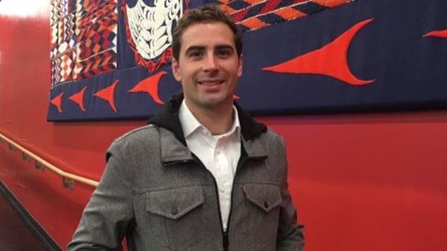 Sean Harris Oliver est debout et sourit devant une murale autochtone dans la salle de nouvelles de Radio-Canada à Vancouver.