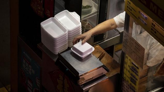 Une pile de contenants en styromousse dans les cuisines d'un petit restaurant.