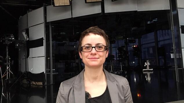 Violaine Langlet porte des lunette et elle est devant le plateau télé de CBC.