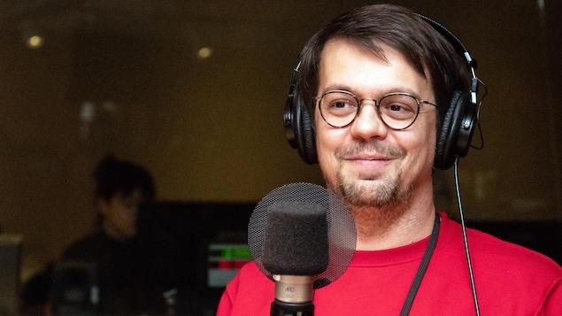 L'auteur et dramaturge Guillaume Corbeil sourit devant un micro.
