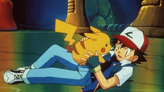 Couché par terre, Ash tient Pikachu dans ses mains en souriant.