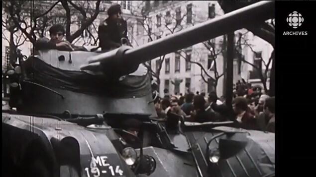 Deux soldats installés dans la tourelle d'un blindé sont entourés par la foule à Lisbonne.