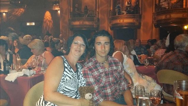 Photographie de famille de Wanny Pelletier et de sa mère assis à une table au milieu d'une salle de spectacle.