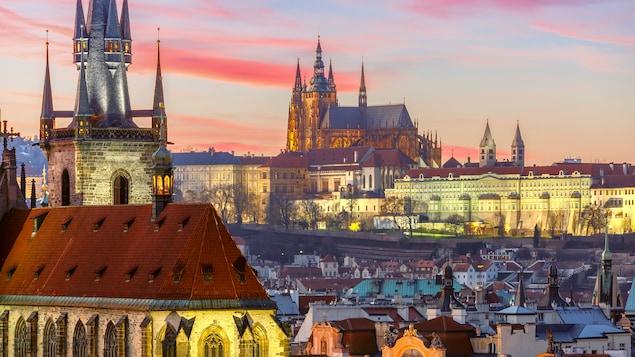 Vue aérienne de la ville de Prague avec la lumière chaude d'un coucher de soleil. On voit une église médiévale en avant plan.