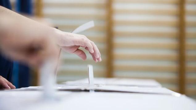 Une personne dépose un bulletin de vote dans une boite.