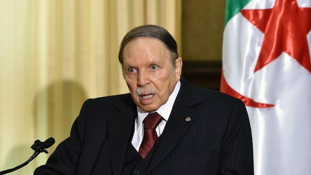 Abdelaziz Bouteflika assis devant un micro, un drapeau algérien derrière lui.