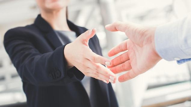 Une femme habillée en veston tend la main à un homme pour une poignée de main.