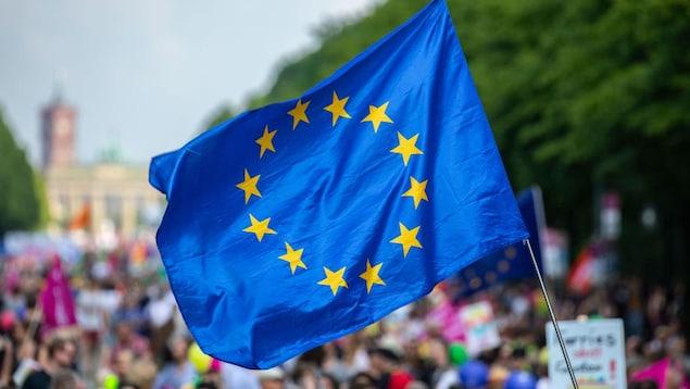 Un manifestant tient le drapeau de l'Union européenne.