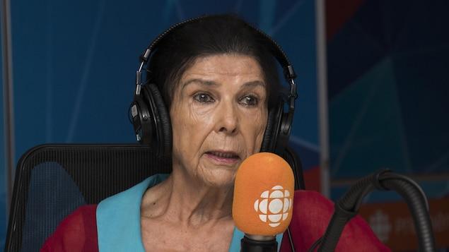 Alanis Obomsawin dans le studio 17 de Radio-Canada, assise devant un micro orange.