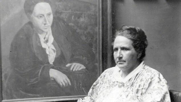 Gertrude Stein assise à coté de son portrait.