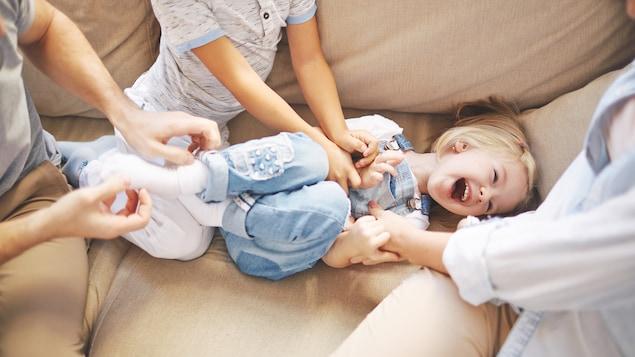 Une jeune fille se fait chatouiller par ses parents et son frère sur un divan