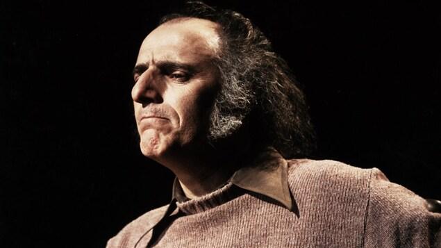 Dans un studio de télévision, en 1977, l'auteur-compositeur québécois Gilles Vigneault est assis sur une chaise, l'air pensif.