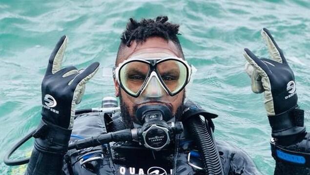 Pierre-Yves Lord en combinaison de plongée dans l'eau. Il regarde la caméra et fait le signe des cornes avec ses mains.